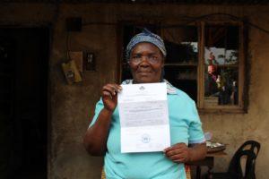 Una veïna mostra la seva carta de notificació de DUAT.